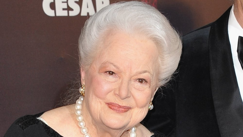 Olivia de Havilland in a black dress and pearls, smiling at a 2011 awards event