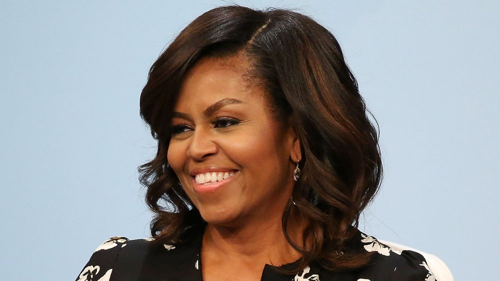 Michelle Obama in a black floral-printed dress, smiling while looking off to the side