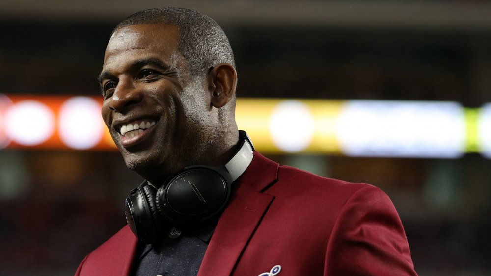 Deion Sanders smiling, while looking off to the side, in a maroon blazer and black polo shirt