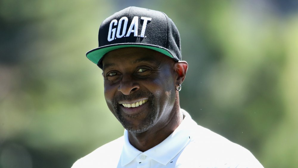 Jerry Rice smiling in a white polo shirt and black GOAT hat