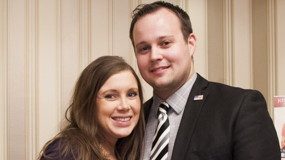 Anna Duggar in a purple dress, smiling and holding her baby bump, and Josh Duggar smiling in a black suit