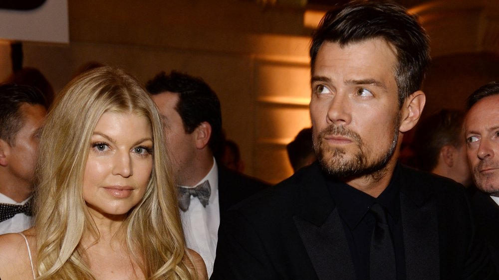 Fergie in a white dress, Josh Duhamel in a black suit, both with serious expressions