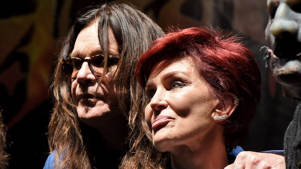 Ozzy Osbourne with his arm around Sharon Osbourne, both with neutral expressions