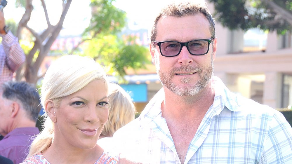 Tori Spelling in a patterned tank top, Dean McDermott in a blue-and-white plaid shirt