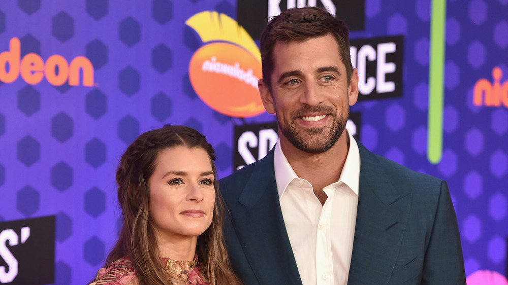 Danica Patrick and Aaron Rodgers smiling at the Nickelodeon Kids' Choice Sports event