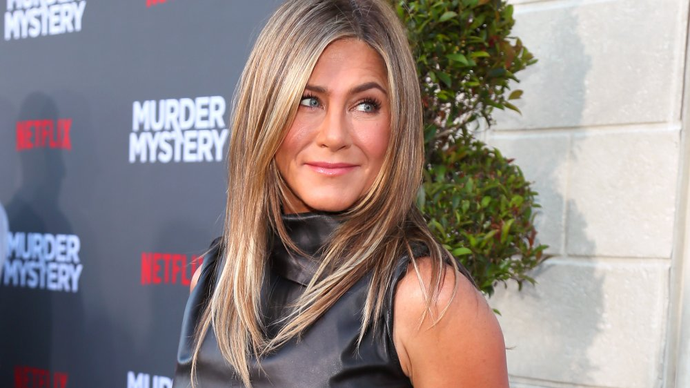 Jennifer Aniston smirking while looking over her shoulder at the Murder Mystery premiere