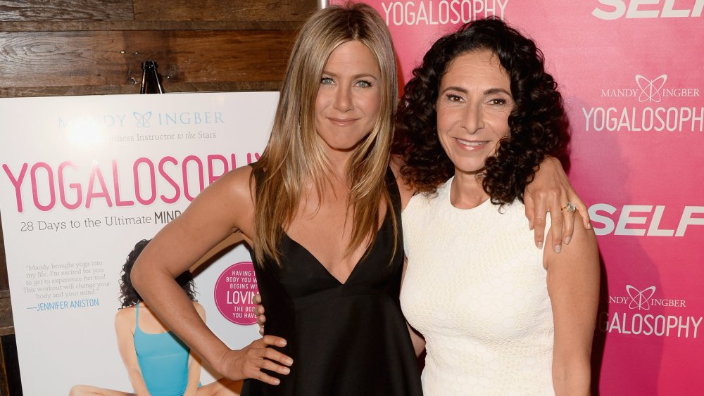 Jennifer Aniston and Yogalosophy inventor Mandy Ingber, smiling and posing arm in arm