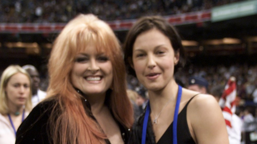 Wynonna Judd, Ashley Judd smiling together at a sports event