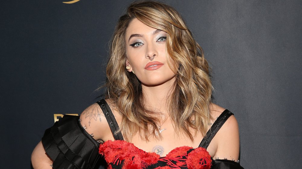 Paris Jackson with curly blonde hair and nose ring
